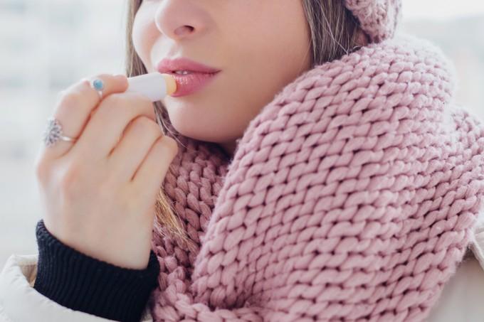 Mulher passando hidratante labial no frio