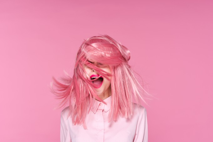 Woman on pink background with flying pink hair, portrait