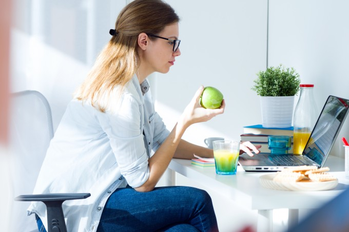 Mulher sentada comendo fruta