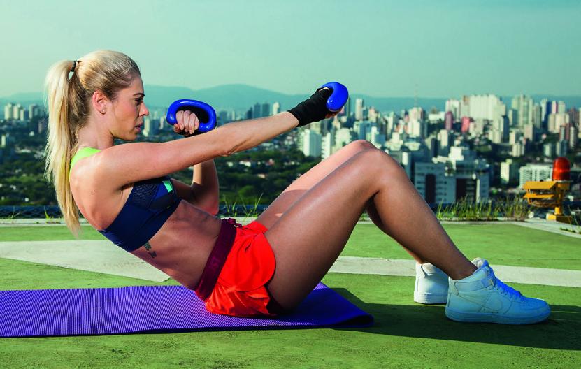 Com as pernas flexionadas e os pés apoiados no solo, segure dois halteres e erga o tronco com os braços na postura de guarda. Dê um soco com cada braço e faça um novo abdominal.
