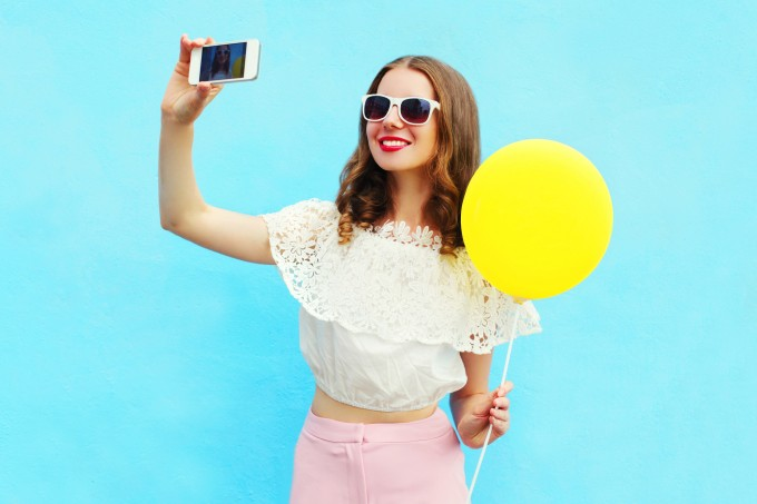 Fashion woman makes self portrait on smartphone with air balloon