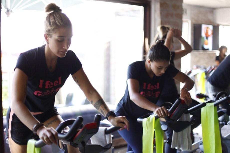 Gabi Pugliesi e Bruna Vilela pedalam na bike durante aula do Studio Velocity