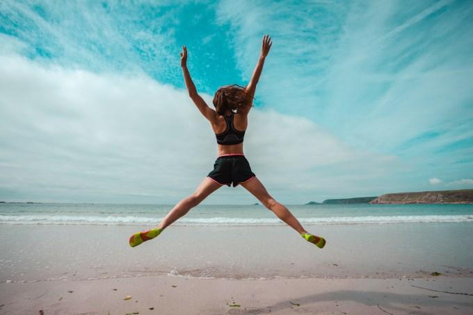 mulher-saltando-praia