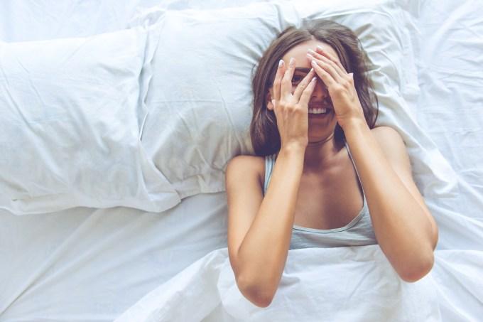 mulher-cama-mao-rosto