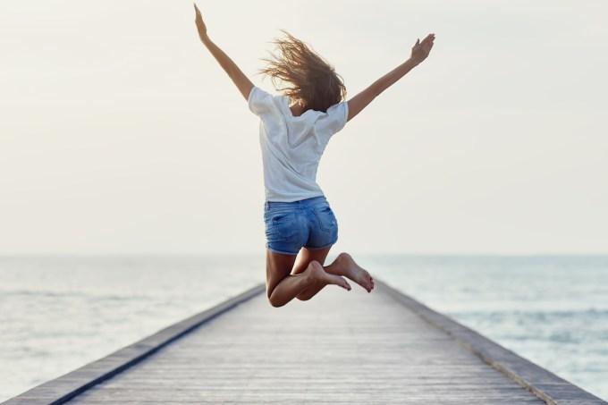 mulher pulando feliz na frente do mar