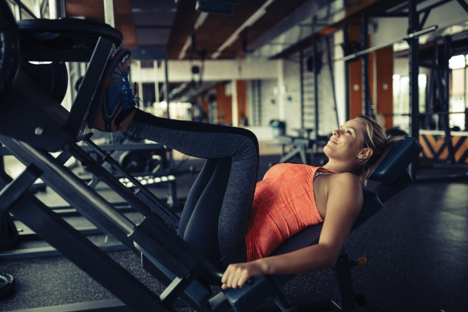 Mulher fazendo leg press na academia