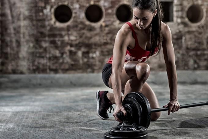 Mulher colocando peso em barra