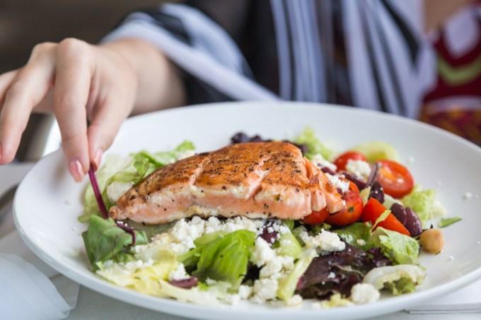 Mulher comendo prato de salada com salmão
