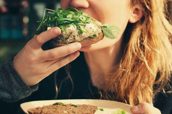 Girl biting veggie sandwich.