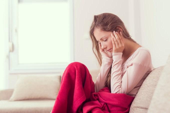 Mulher sentada no sofá com dor de cabeça