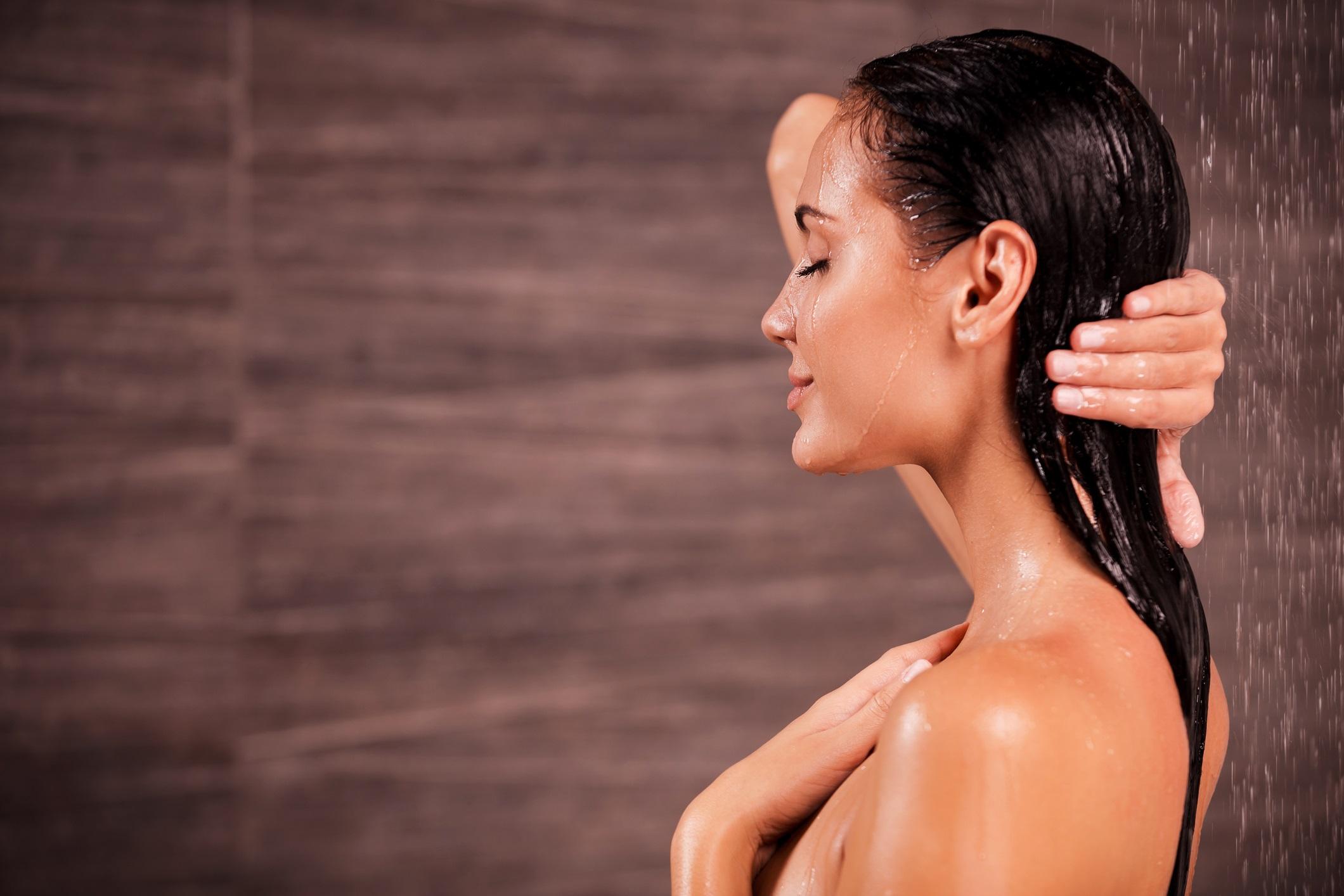 Mulher no chuveiro com o cabelo molhado