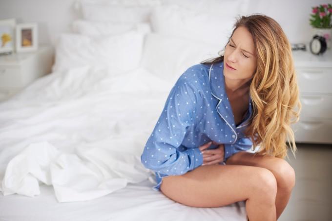 Mulher sentada na cama com dor de barriga