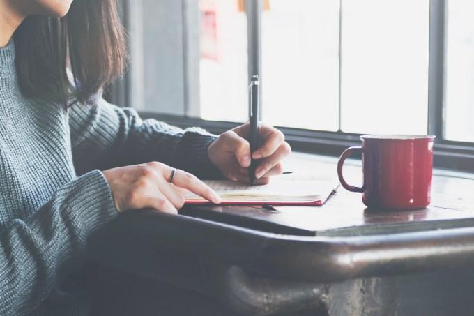 Mulher sentada escrevendo em caderno