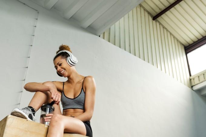 mulher descansando durante treino sentada em cima de caixa de crossfit com fones de ouvido e garrafa de água