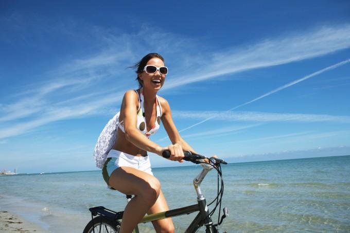 Mulher andando de bicicleta na praia