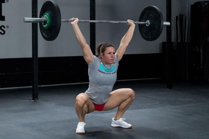Mulher agachando com barra acima da cabeça no treino de crossfit