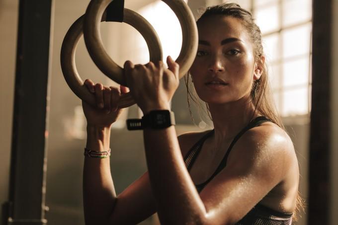 mulher segurando argolas no treino de crossfit enquanto descansa