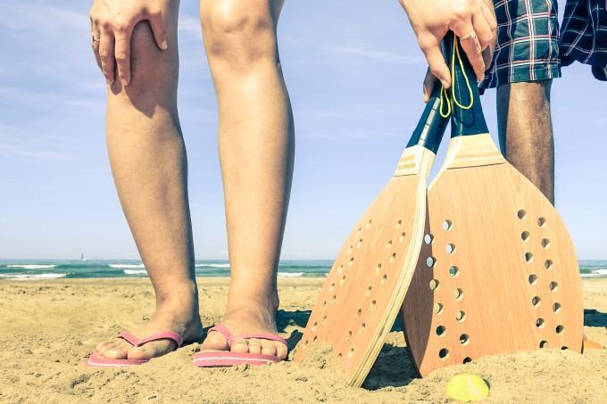 mulher com raquete de beach tennis na praia