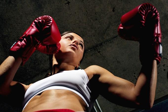 Mulher lutando boxe com luvas