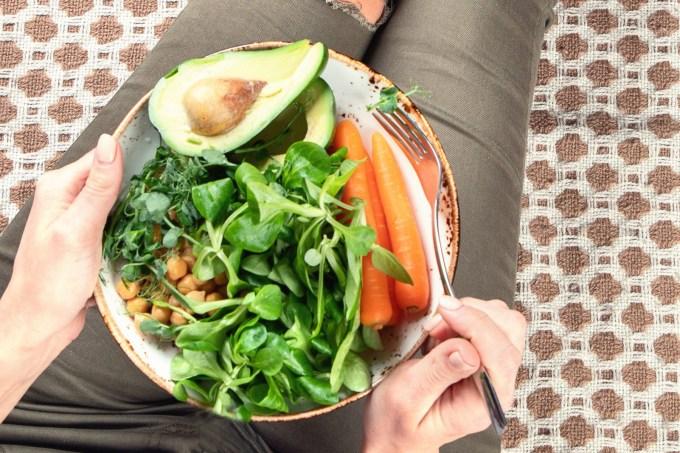Mulher segurando prato vegetariano