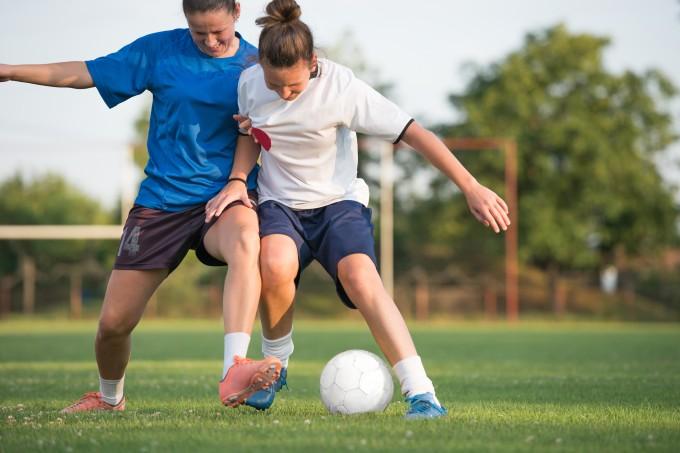 Mulheres jogando futebol com bola