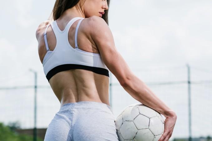 Mulher de costas segurando bola de futebol