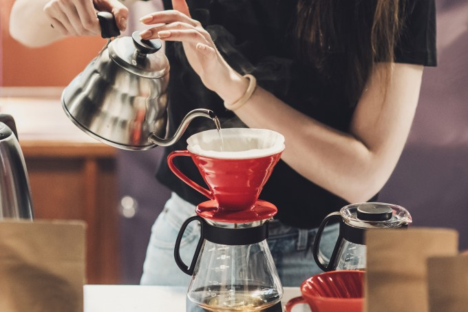 Young women barista at work in a cafe. Preparing pour over coffee