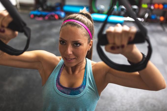 Mulher praticando exercício no TRX