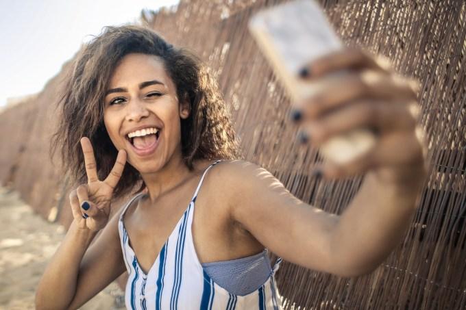 Mulher tirando uma selfie sorrindo na praia