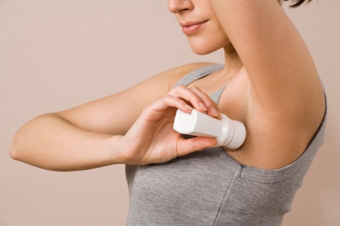Mulher aplicando desodorante nas axilas