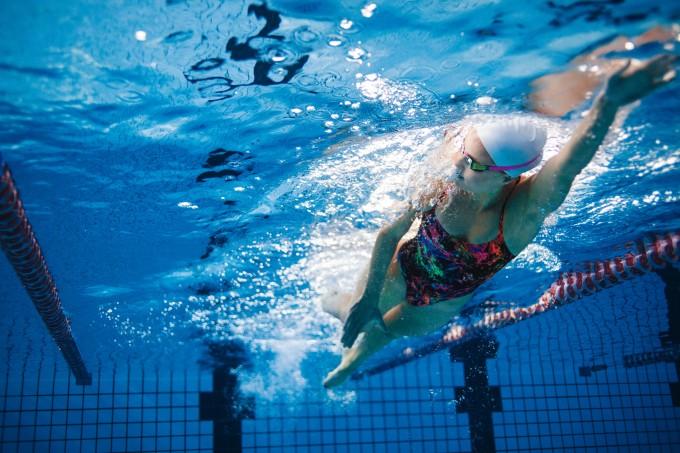 Mulher nadando numa aula de natação na piscina