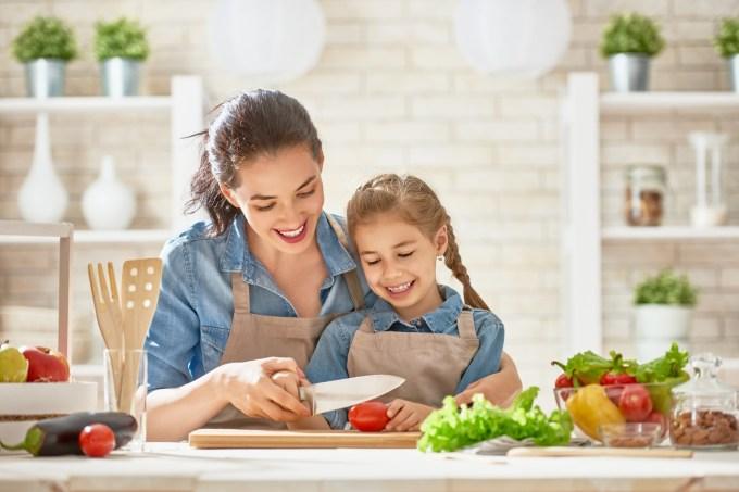 mãe fazendo salada com a filha