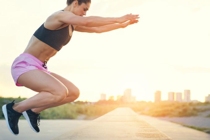 Imagem meramente ilustrativa mostra uma mulher de top e short rosa realizando agachamento com salto