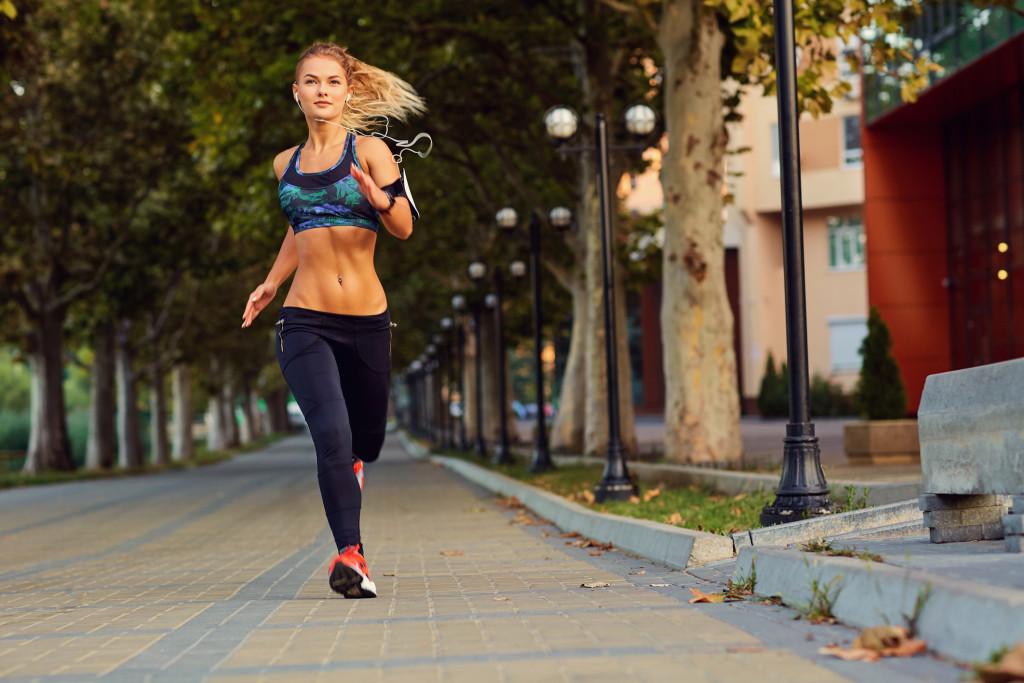 Imagem meramente ilustrativa mostra uma mulher loira correndo ao ar livre para ilustrar exercícios para pernas e bumbum