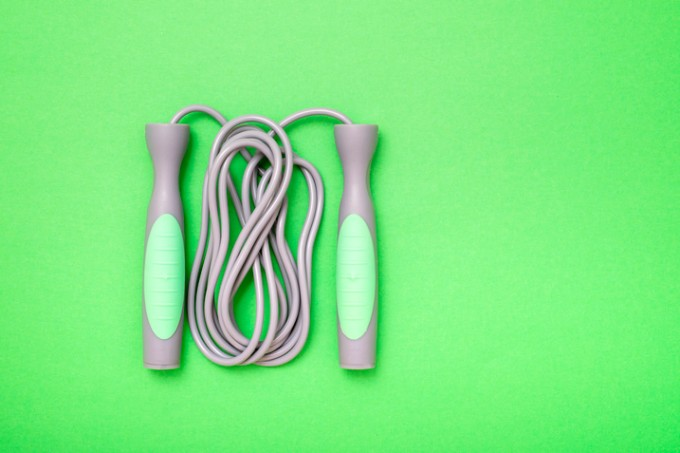 High Angle View Of Jumping Rope On Green Background