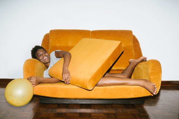 woman-lying-on-orange-sofa-3621486