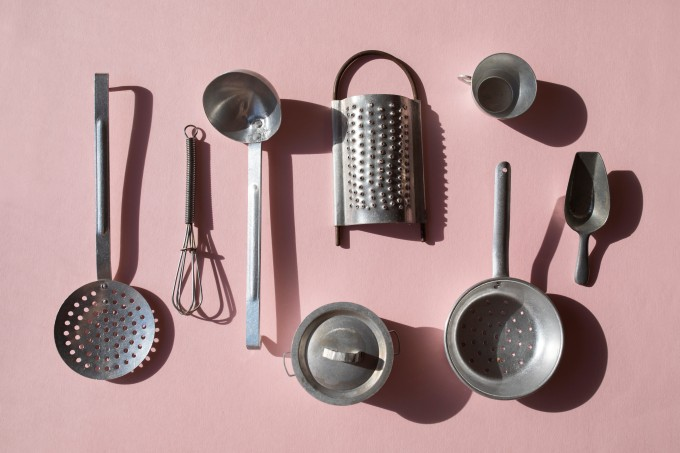 Vintage kitchen utensils on the pink background