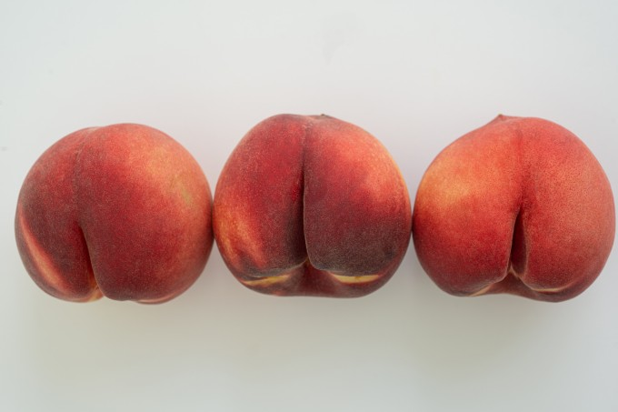 A row of white peaches on white surface