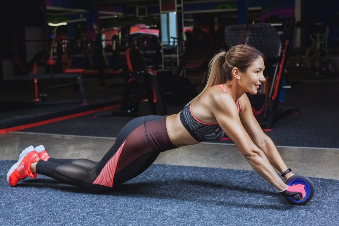 Slim, bodybuilder girl, does the exercises with Ab Wheel in the gym.