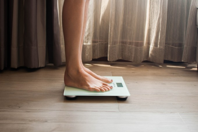 A young woman is weighing herself in a weighing scale