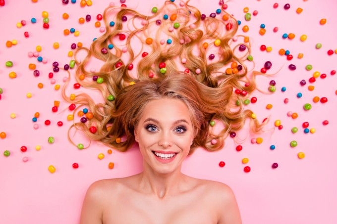 Vertical side profile top above high angle view photo pretty she her lady lying down naked sweets ideal hair chocolate colored little candies everywhere isolated pink background