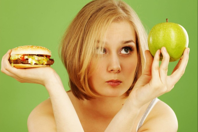 Contemplative Woman Holding Apple and Hamburger Deciding