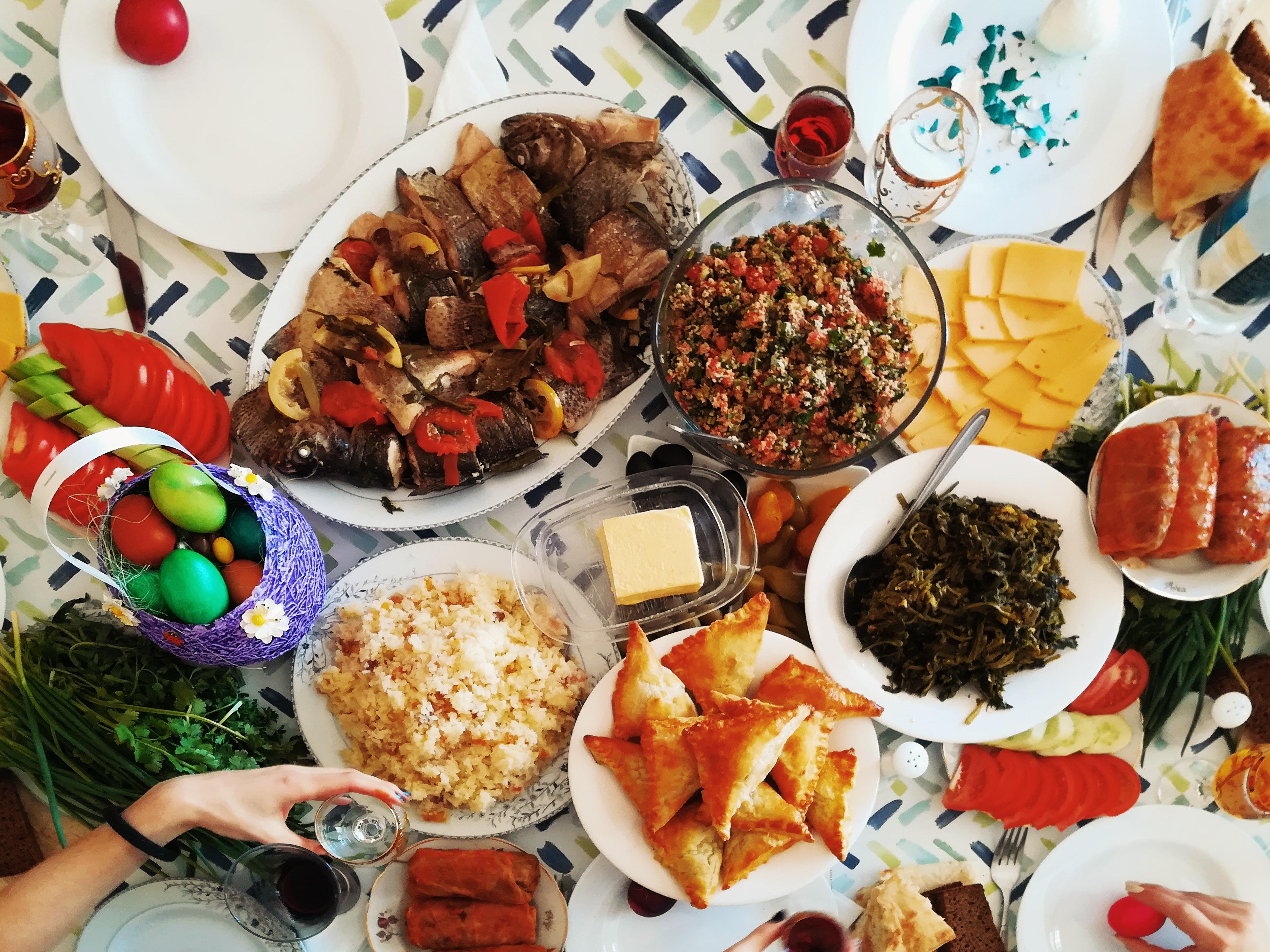 Mesa com diversos pratos de natal, no canto uma mão segura uma taça de bebida