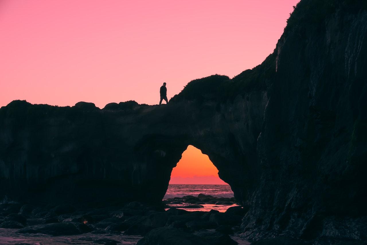 Foto de uma pedreira em cima ao mar, tem uma pessoa em cima e o céu ao fundo está rosa, como se fosse fim da tarde