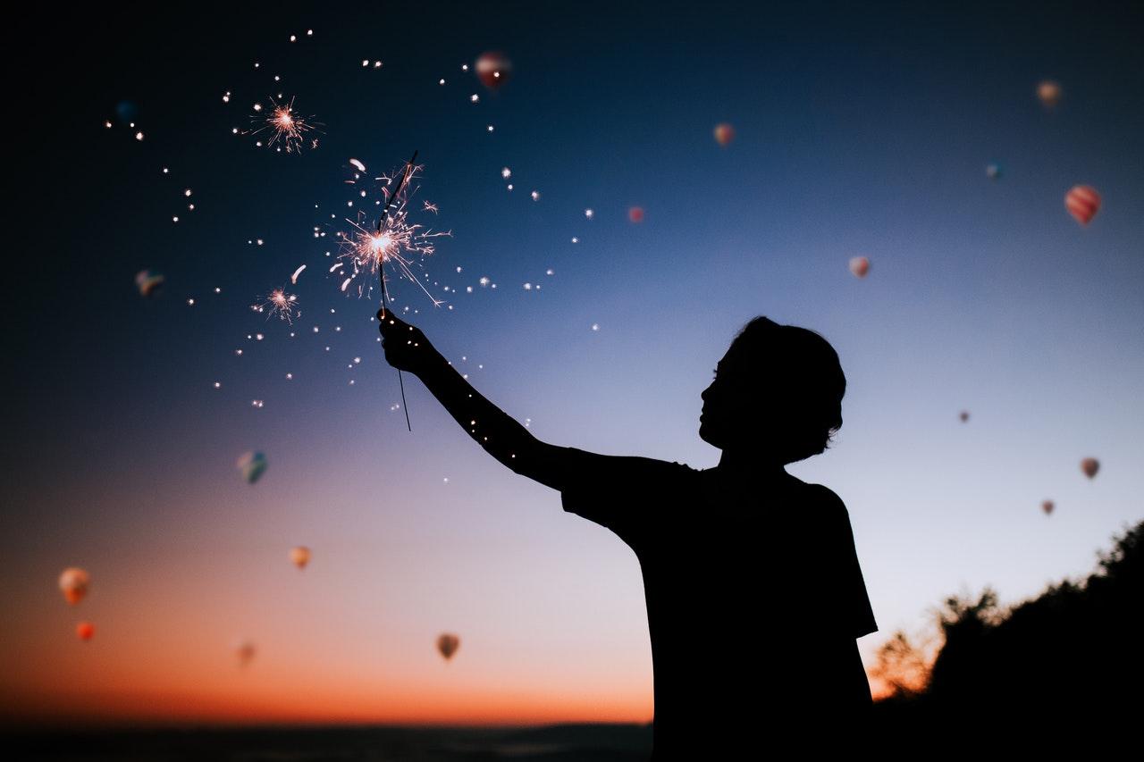 Silhueta de uma pessoa com o céu de fim da tarde ao fundo. A pessoa segura uma vela com a mão para cima