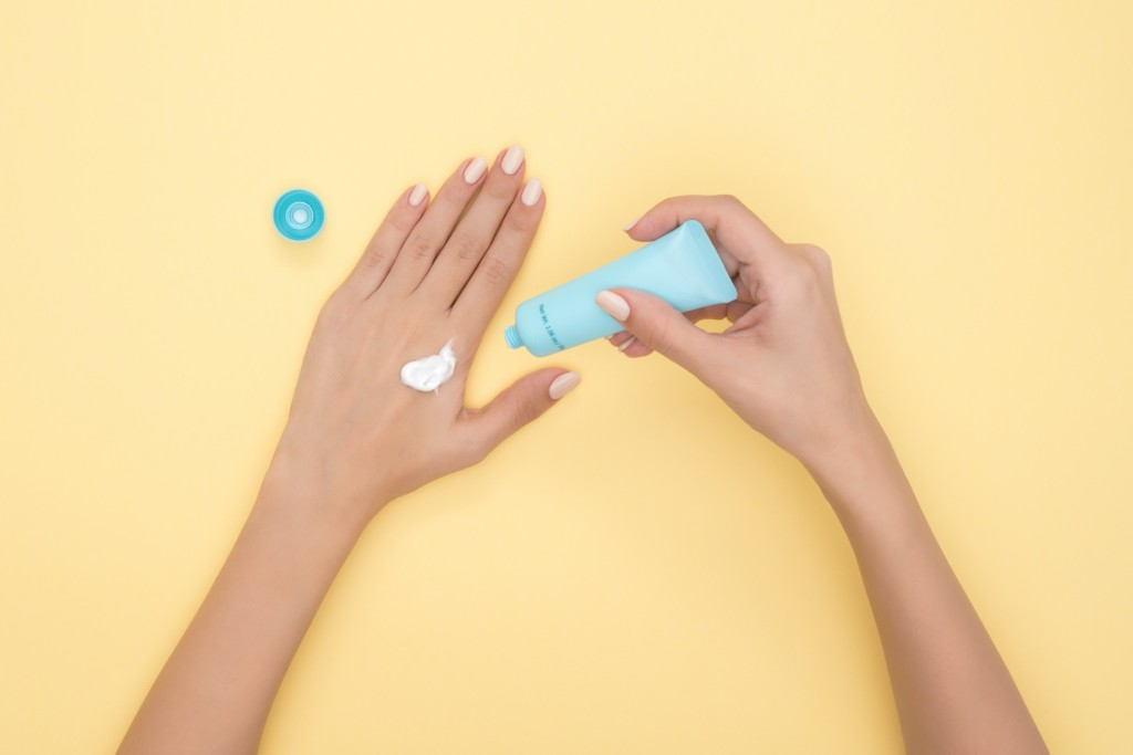Um fundo laranja pastel com duas mãos brancas sobre, onde uma delas está segurando uma embalagem azul clara e na outra mão um pouco de protetor está nas costas da mão, próximo ao indicador.