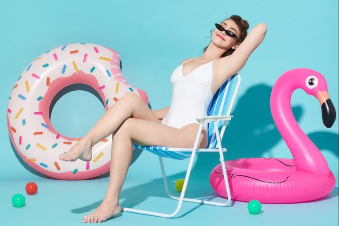 Portrait Of Young Woman Wearing Swimwear While Sitting On Chair Against Turquoise Backdrop