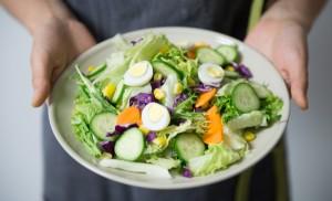 Duas mãos brancas segurando um prato branco com alface, pepino, ovos, cenoura e grão-de-bico.