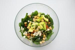 Uma salada de folhas verdes com grão de bico, pedaços de abacate, cebola e tomate em um recipiente transparente em um fundo branco