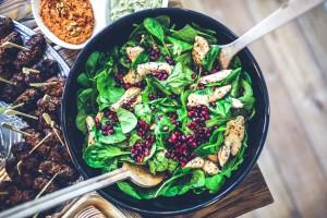 Salada de folhas verdes com frango em um recipiente escuro e talheres de metal posicionados dentro da tigela